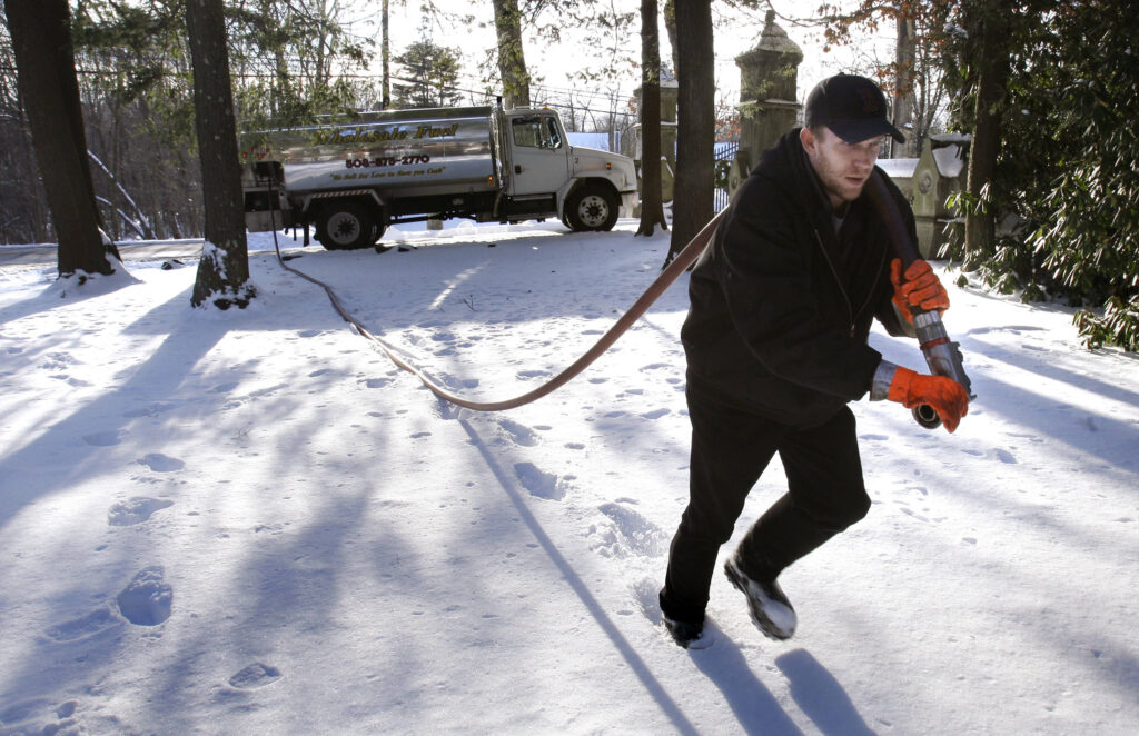 FILE - In this Jan. 5, 2010 file photo, Jason Kilpatrick of Wholesale Fuel hauls a hose across a snow covered yard while delivering home heating oil in Framingham, Mass. Natural gas prices climbed Monday, Feb. 8 as another winter storm was expected to dump even more snow on the East Coast. (AP Photo/Charles Krupa, File)